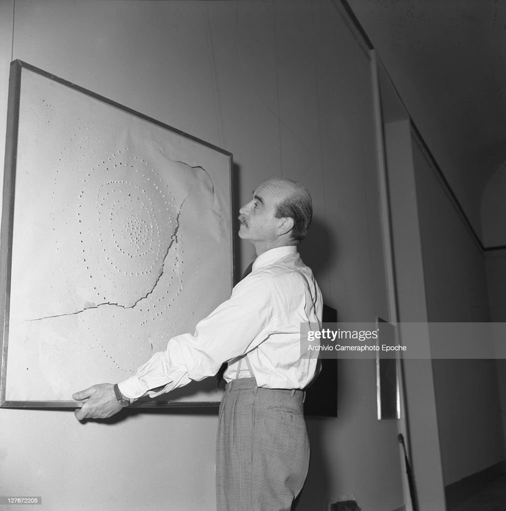 Italian painter <a gi-track='captionPersonalityLinkClicked' href=/galleries/search?phrase=Lucio+Fontana&family=editorial&specificpeople=827690 ng-click='$event.stopPropagation()'>Lucio Fontana</a> during the Art Biennale, Venice, 1954.