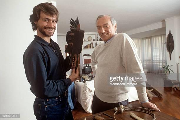 Italian paleontologist and science journalist Alberto Angela smiling holding a tribal mask next to his father Italian TV presenter Piero Angela 1990s