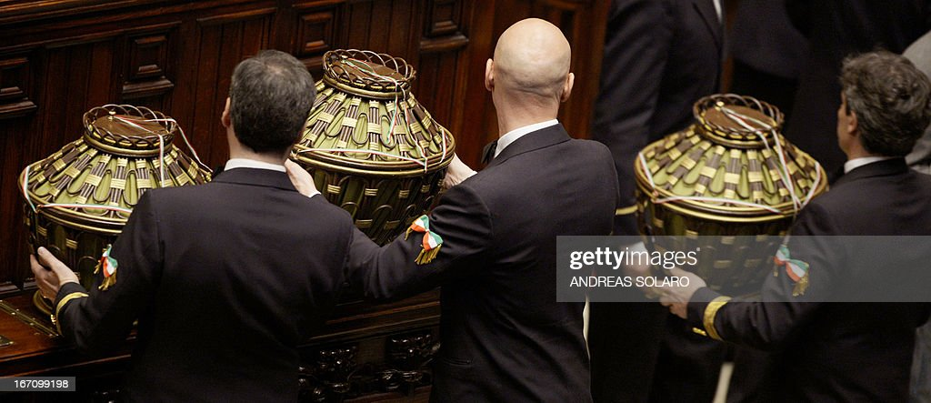 Italian Parliament ushers carry ballot boxes in the Italian Parliament on April 20, 2013 during the election of Italy's President. Italy's 87-year-old President Giorgio Napolitano said on Saturday said he would run for a second term despite earlier ruling out the prospect, following an appeal from the main parties to help defuse an increasingly tense political crisis. 'I consider it necessary to offer my availability,' Napolitano said in a statement, as bickering lawmakers prepared for a sixth round of voting in parliament that he is now expected to win by a large margin. AFP PHOTO / ANDREAS SOLARO