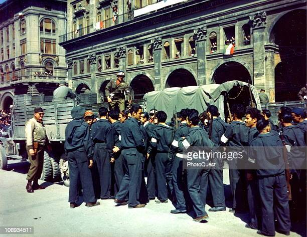 Italian partisans hands over their weapons to American MPs as they disband their units in front of the Palazzo dei Banchi in the Piazza Vittorio...