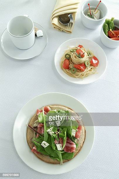 Italian pasta and salad dishes with coffee cup