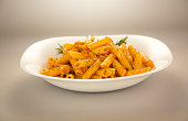 penne rigate milanese served in a plate