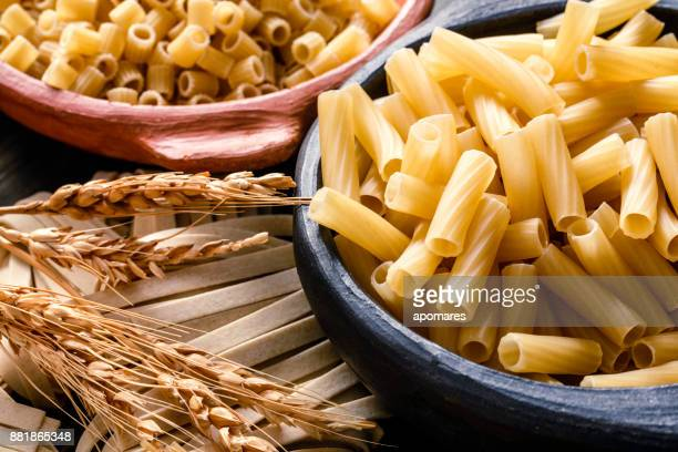 Italian pasta on rustic wooden table in a kitchen. Close-up on Rigatoni pasta.