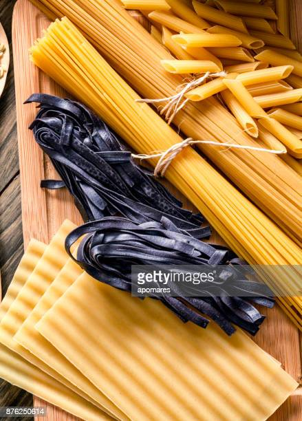 Italian pasta on rustic wooden table in a kitchen. Including black Fetuccini.