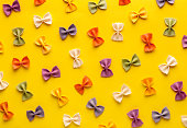 Italian pasta pattern on a yellow background. Various colors of bow tie farfalle pasta viewed from above. Top view. Repetition. Full frame