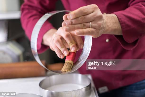 Italian pastry making patisserie baking confectioner: lubricating cake rings with butter