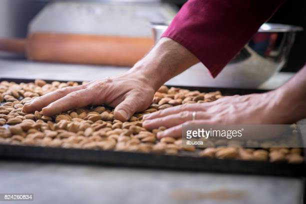 Italian pastry making patisserie baking confectioner: Toasting almonds on baking tray