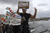 Italian peace activist Vittorio Arrigoni holds up a box of medicine as he celebrates the arrival of 20metre ship 'Dignity' that departed from Cyprus...