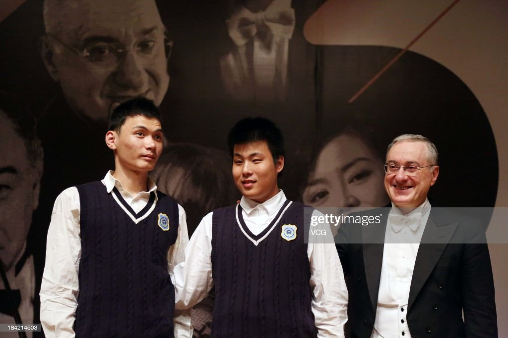 Italian pianist Michele Campanella pose with blind children of Nanjing School for the Blind during the Jiangsu International Piano Master Music Festival at Nanjing University of the Arts on October 11, 2013 in Nanjing, China.