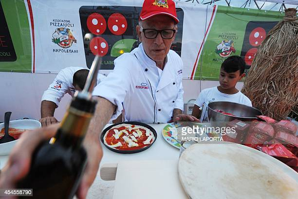 Italian pizza maker masterchef Gennaro Cervone gives a lesson of homemade pizza during the pizza festival in Naples on September 3 2014 AFP...