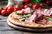 Italian pizza with ham and asparagus, selective focus