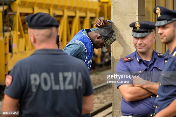 Italian police officers and an aid worker wait for a train bound north to Munich at the station on September 3 2015 in Bressanone Italy Italian...