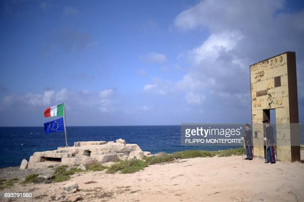 Italian police officers stand by the 'Door of Europe' on the island of Lampedusa on June 7 during a European Relationship for Mediterranean Security...