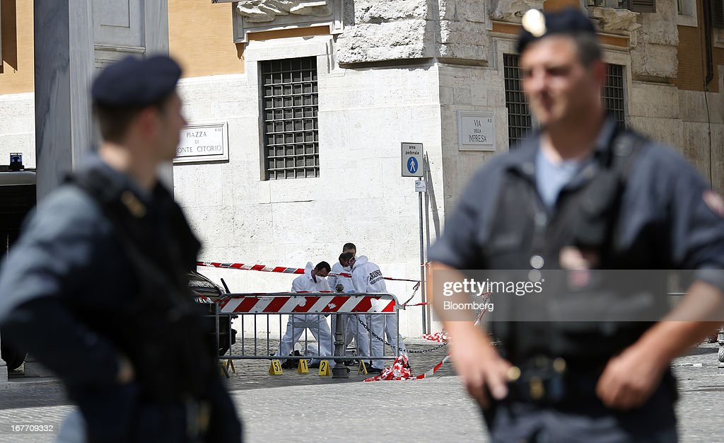 Italian police officers stand on duty as a Carabinieri forensics unit look for evidence at an intersection following a shooting outside the Chigi Palace in Rome, Italy, on Sunday, April 28, 2013. Two Italian police officers were shot outside the prime minister's office in Rome today by a lone gunman while the country's new premier, Enrico Letta, was being sworn in across town, police said. Photographer: Alessia Pierdomenico/Bloomberg via Getty Images