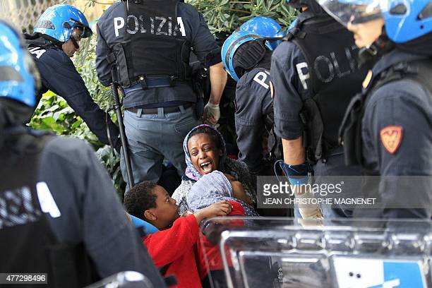 Italian police officers surround a family of migrants during an operation to remove them from the ItalianFrench border in the Italian city of...