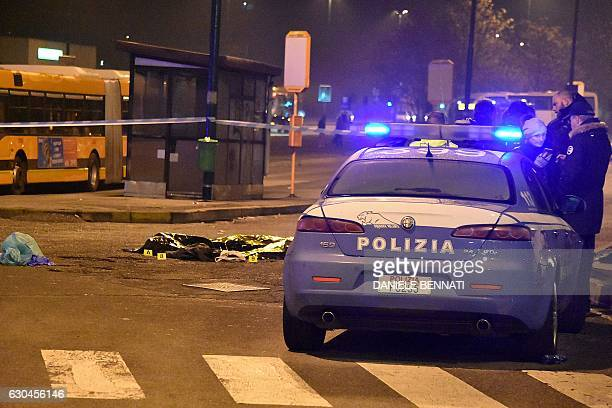 Italian police stand by the body of suspected Berlin truck attacker Anis Amri after he was shot dead in Milan on December 23 2016 The Tunisian man...