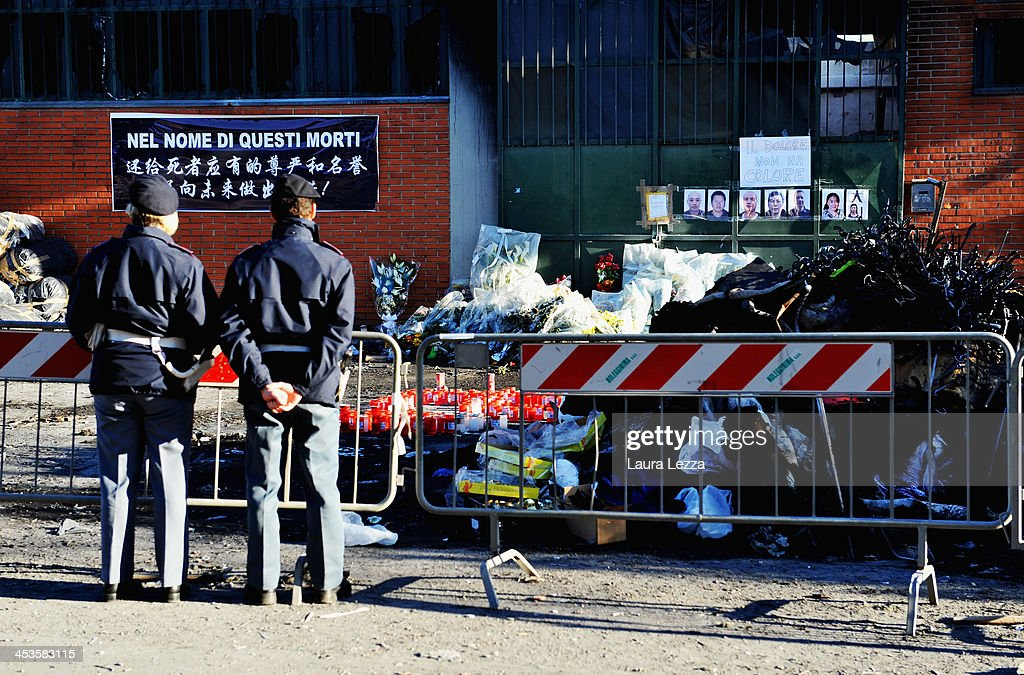 Italian Police stand outside a clothing factory where seven Chinese workers were burned to death on December 4, 2013 in Prato, Italy. Seven people died and three were injured December 1, when a Chinese clothing factory in the industrial district of the Italian town of Prato in Tuscany burned, killing the workers trapped in a factory dormitory, where workers sleep, eat, and work.