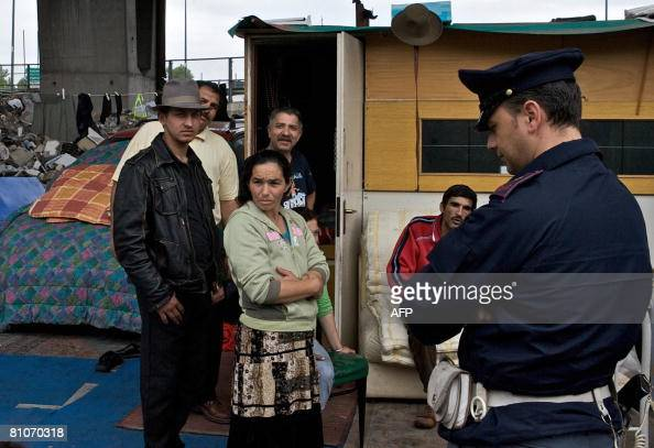 Italian policeman speaks with a Rom nomad at a Rom' camp in Ponticelli a quarter of Naples south of Italy on May 13 2008 Early morning a Neapolitan...
