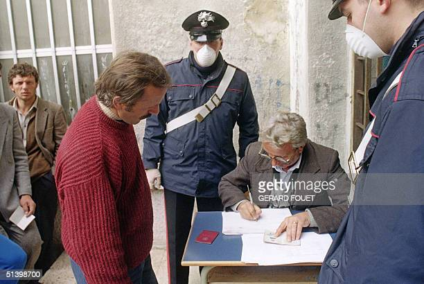 Italian policemen wearing masks for fear of epidemics register Albanian refugees at the Brinidisi port 09 March 1991