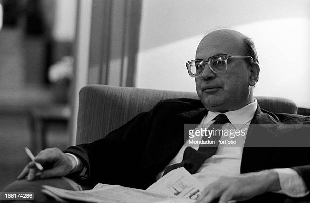 Italian politician and President of the Council of Ministers of the Italian Republic Bettino Craxi smoking seated in an armchair before the memorial...