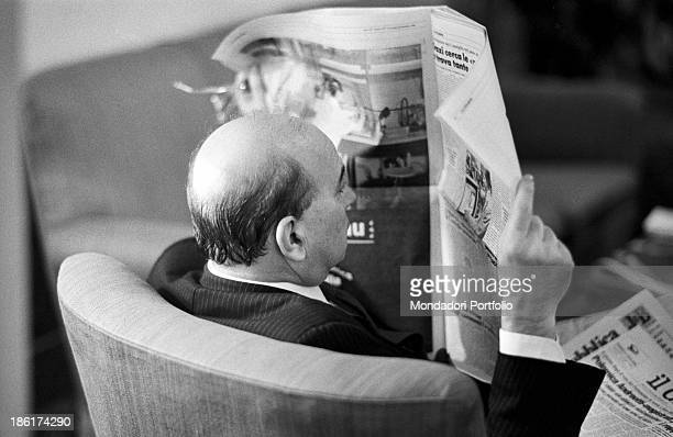 Italian politician and President of the Council of Ministers of the Italian Republic Bettino Craxi reading a newspaper before the memorial...