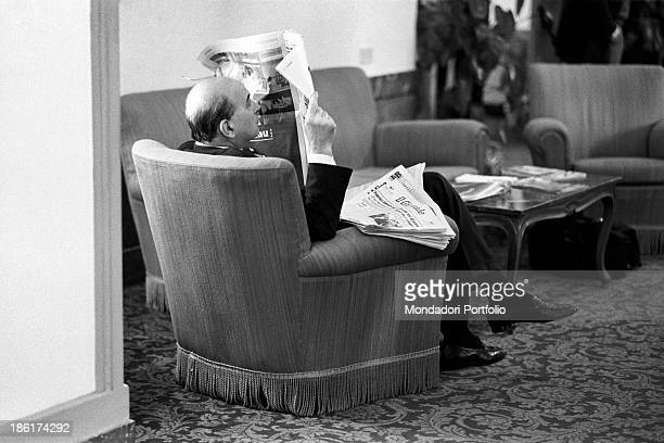 Italian politician and President of the Council of Ministers of the Italian Republic Bettino Craxi reading seated in an armchair before the memorial...