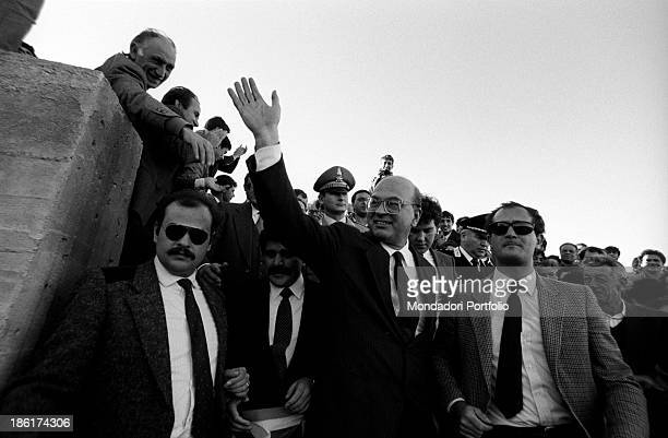 Italian politician and President of the Council of Ministers of the Italian Republic Bettino Craxi escorted by his bodyguards greeting the people...