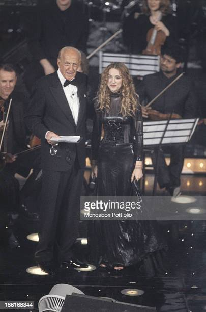 Italian presenter and actor Raimondo Vianello smiling with American singersongwriter Madonna at the 48th Sanremo Music Festival Sanremo February 1998