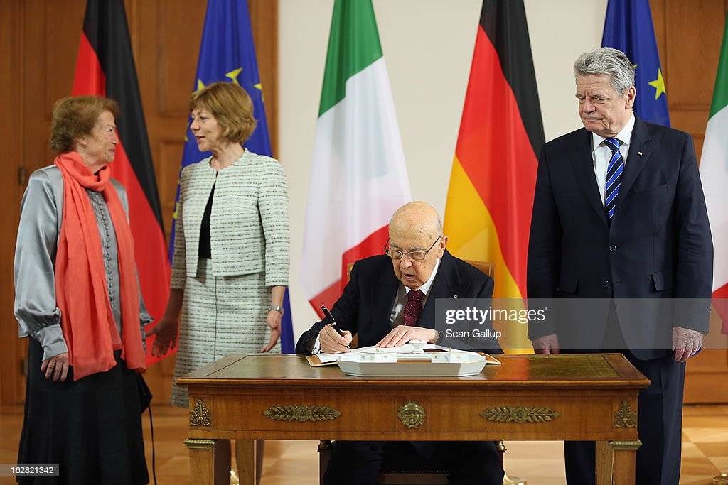 Italian President Giorgio Napolitano signs a guest book at Schloss Bellevue palace as German President Joachim Gauck, Italian First Lady Clio Napolitano (L) and Gauck's partner Daniela Schadt look on on February 28, 2013 in Berlin, Germany. Napolitano, who is on a three-day visit to Germany, cancelled his scheduled dinner with German Social Democrat and chancellor candidiate Peer Steinbrueck the evening before after Steinbrueck made public comments decribing Italian election frontrunners Silvio Berlusconi and Beppe Grillo as political 'clowns'.