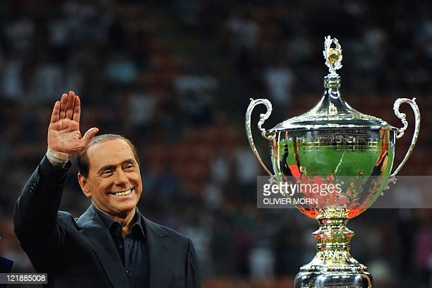 Italian President of Council Silvio Berlusconi waves to spectators after the Trophee Luigi Berlusconi match AC Milan against Juventus on August 21 in...