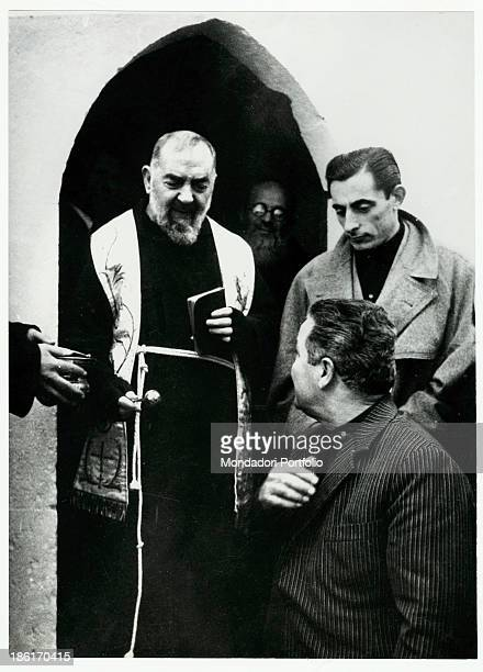 Italian priest Padre Pio of Pietrelcina blessing a man Italian cyclist fausto Coppi watching the scene Italy 1959