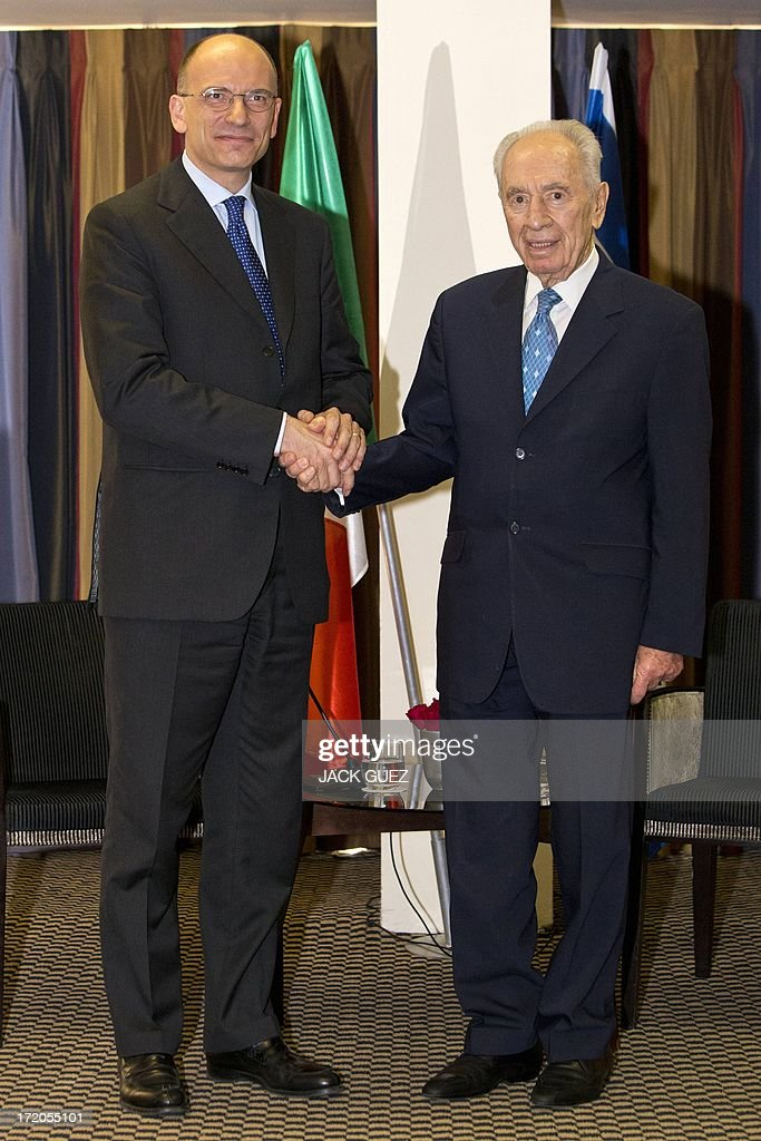 Italian Prime Minister Enrico Letta (L) shakes hands with Israeli President Shimon Peres (R) during a diplomatic working meeting in the Mediterranean coastal city of Tel Aviv on July 01, 2013. The two will discuss strengthening strategic relations between Israel and Italy and cooperation in a range of fields.