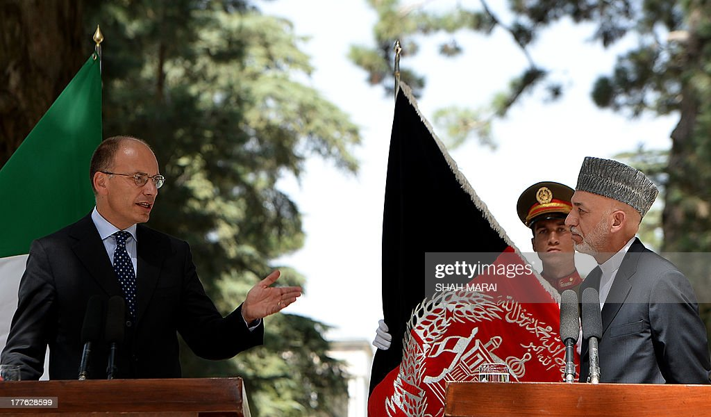 Italian Prime Minister Enrico Letta (L) speaks during a joint press conference as Afghan President Hamid Karzai looks on at the Presidential palace in Kabul on August 25, 2013. Letta visited the base of the Italian contingent in Herat on his arrival in the country - Italy has around 3,000 soldiers in Afghanistan as part of NATO's International Security Assistance Force (ISAF). AFP PHOTO/ SHAH Marai