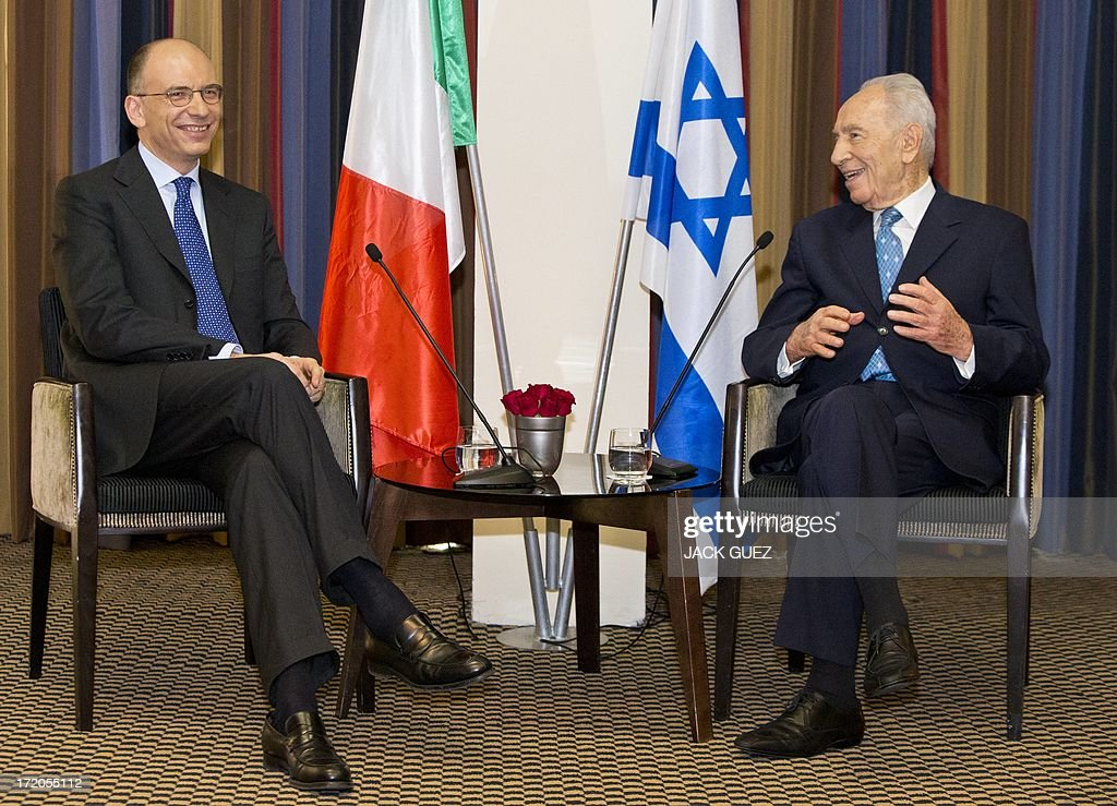 Italian Prime Minister Enrico Letta (L) talks to Israeli President Shimon Peres (R) during a diplomatic working meeting in the Mediterranean coastal city of Tel Aviv on July 01, 2013. The two will discuss strengthening strategic relations between Israel and Italy and cooperation in a range of fields.