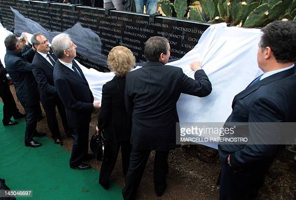 Italian Prime Minister Mario Monti and officials unveil a commemoration plate during a ceremony at a memory garden ' giardino della legalita' marking...