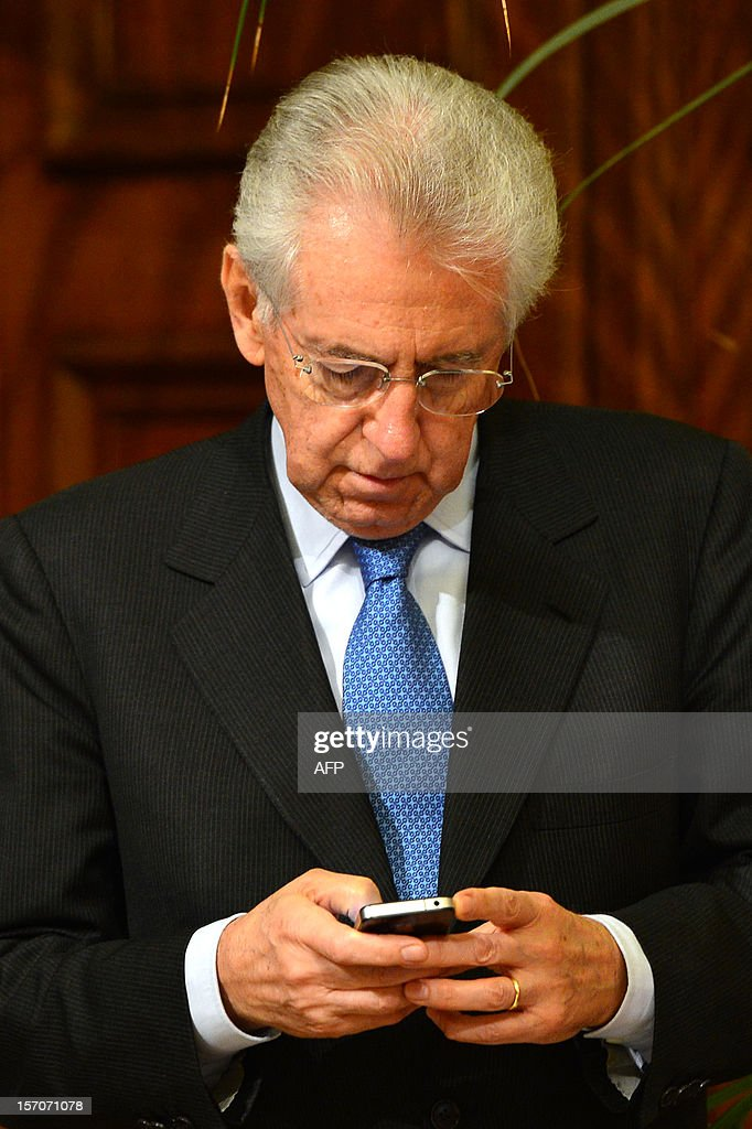 Italian Prime Minister Mario Monti looks at his mobile phone prior a meeting with a top political leader on November 28, 2012 at Palazzo Chigi in Rome. AFP PHOTO / GABRIEL BOUYS