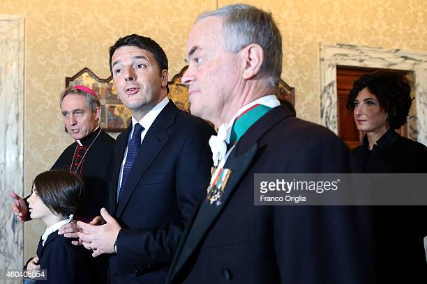 Italian Prime Minister Matteo Renzi and first lady Agnese Landini flanked by Prefect of the Pontifical House and former personal secretary of Pope...