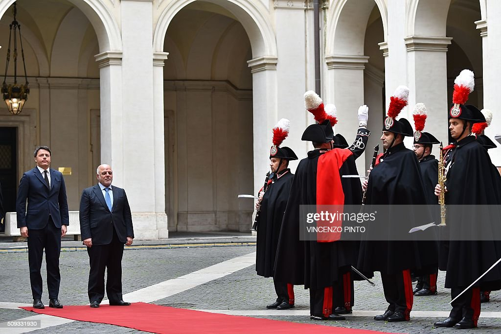 Italian Prime Minister Matteo Renzi (L) and Iraq's Prime Minister Haider al-Abadi review a guard of honor before their meeting on February 10, 2016 at the Palazzo Chigi in Rome. / AFP / VINCENZO PINTO