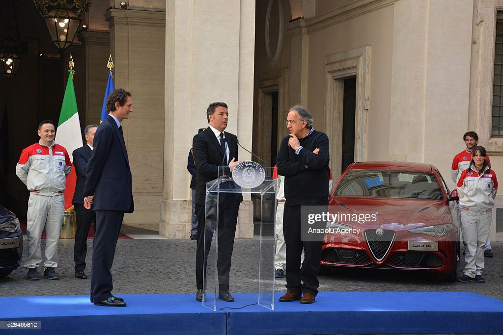 Italian Prime Minister Matteo Renzi (C) delivers a speech as President of FCA John Elkann (L) and FCA's CEO Sergio Marchionne (R) stand next to him during Italian automotive company Fiat-Chrysler Group (FCA) introduces Alfa Romeo's new brand sports car 'Giulia' with a ceremony at the yard of Chigi palace in Rome, Italy on May 5, 2016.