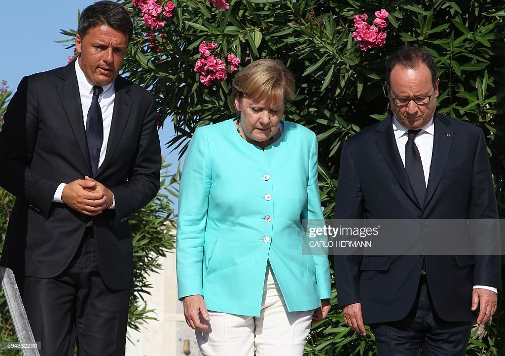 TOPSHOT Italian Prime Minister Matteo Renzi German Chancellor Angela Merkel and French President Francois Hollande arrive to pay their respects at...