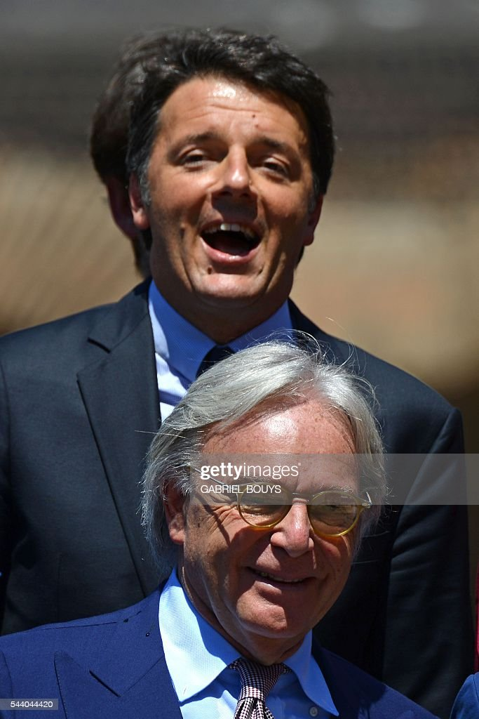 Italian Prime Minister Matteo Renzi (up) jokes with Diego della Valle, CEO of luxury shoe brand Tod's, during a press conference on July 1, 2016 in Rome to announce the end of the restoration of the façade of the Colosseum that his company funded. / AFP / GABRIEL