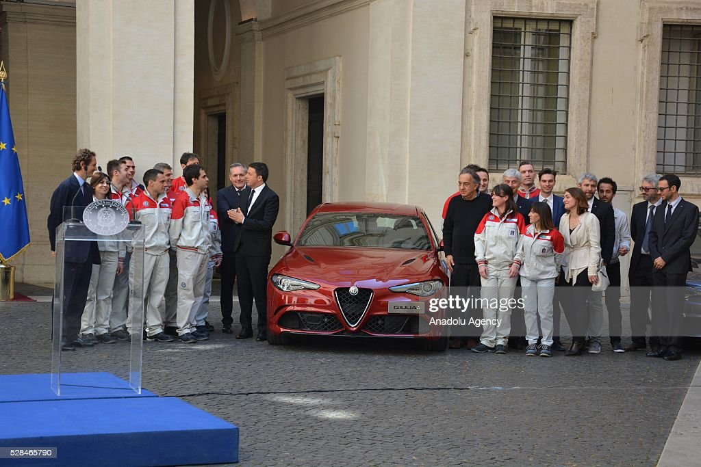 Italian Prime Minister Matteo Renzi, President of FCA John Elkann, FCA's CEO Sergio Marchionne and engineers of the 'Giulia' pose for a family photo as Italian automotive company Fiat-Chrysler Group (FCA) introduces Alfa Romeo's new brand sports car 'Giulia' with a ceremony at the yard of Chigi palace in Rome, Italy on May 5, 2016.
