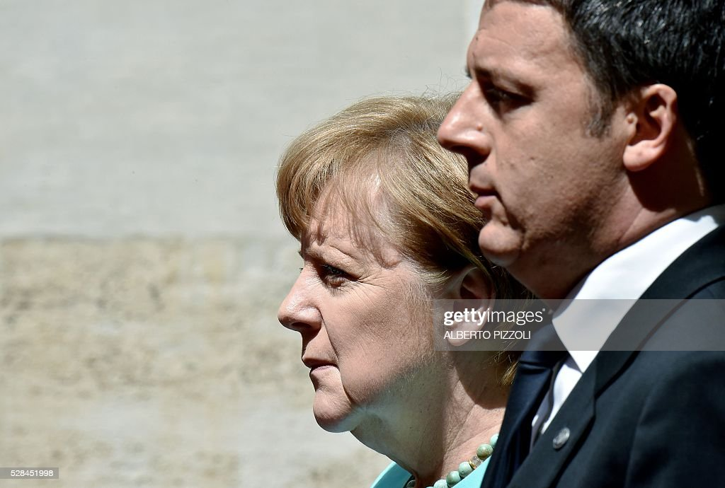 Italian Prime Minister Matteo Renzi (R) stands next to German Chancellor Angela Merkel upon her arrival at Rome's Palazzo Chigi on May 5, 2016. EU president Donald Tusk travels to Rome Thursday with fellow EU institution leaders and German Chancellor Angela Merkel for two days of talks likely to focus on next steps in Europe's migrant crisis. Prime Minister Matteo Renzi, who fears Italy becoming the new migrant frontline after the closure of the Balkan route, will host the first day of talks, followed by Pope Francis on Friday. PIZZOLI