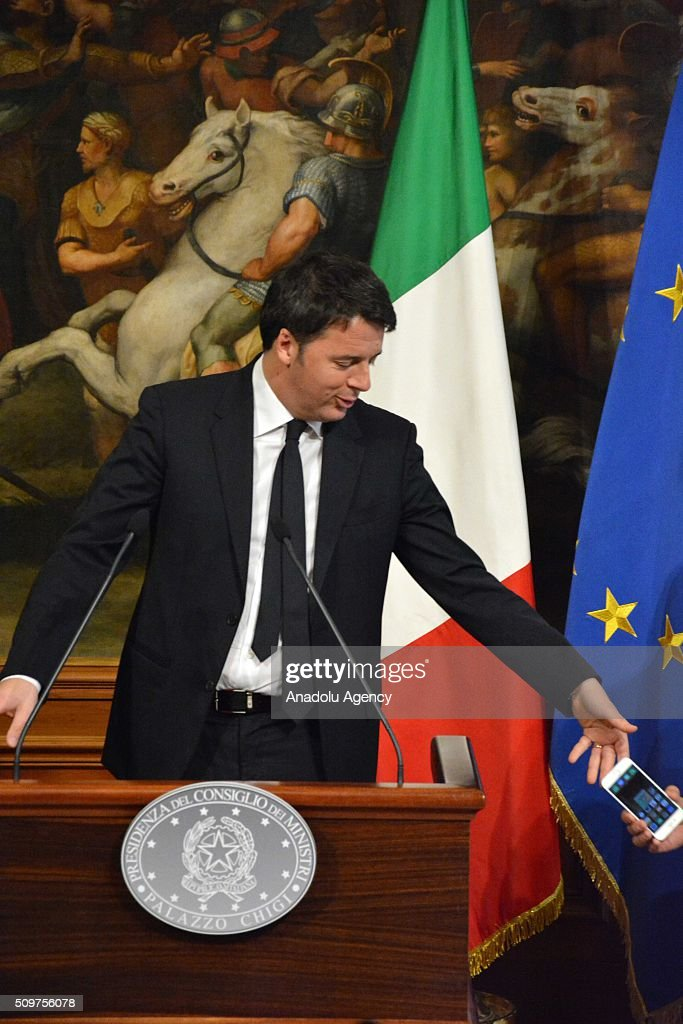 Italian Prime Minister Matteo Renzi takes his mobile phone back after he dropped it to floor during a joint press at Chigi palace in Rome, Italy on February 12, 2016.