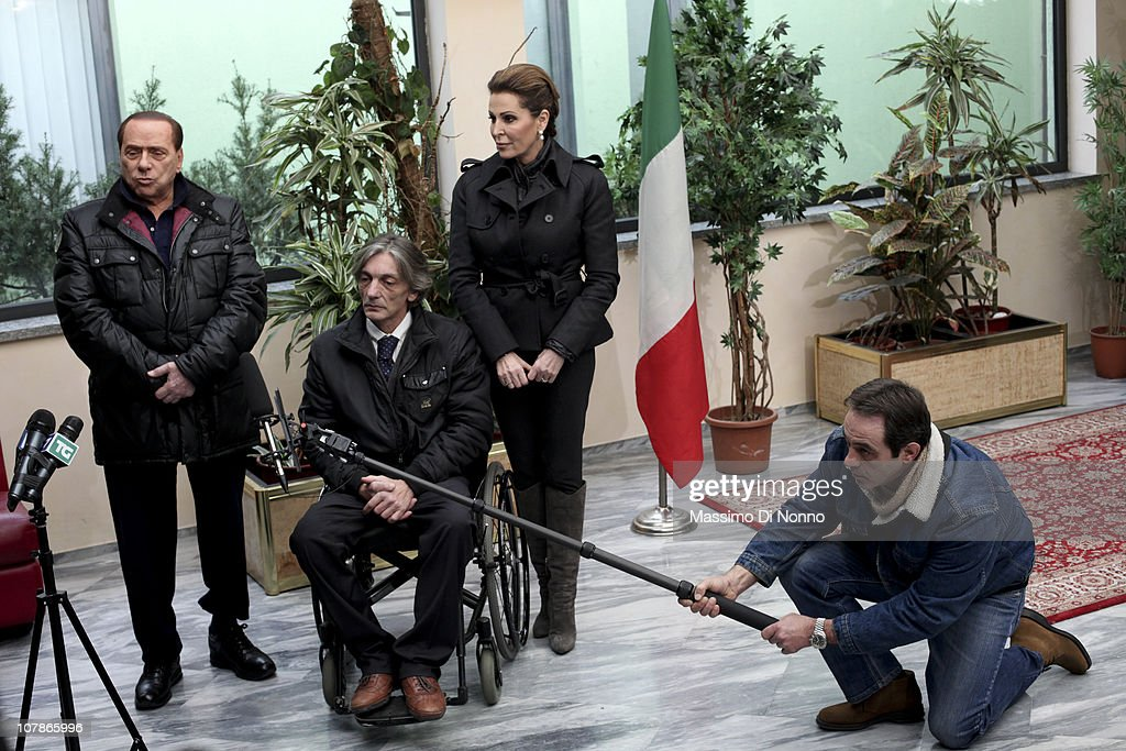 Italian Prime Minister Silvio Berlusconi (L) and Italian politician Daniela Santanche (R) face a media gathering alongside Alberto Torregiani, the son of Pierluigi Torregiani, at Linate military airport on January 04, 2011 in Milan, Italy. Alberto Torregiani was shot in the back and was left paralysed during the same gunfight in which his father jeweler Pierluigi Torregiani was killed by militant group PAC (Armed Proletarians for Communism) in 1979. Italy has recalled its ambassador to Brazil to following former Brazilian President Luiz Inacio Lula da Silva's decision on his final day in office not to approve the extradition of Cesare Battisti, deemed responsible for the attack and convicted for a string of murders in the 1970s for which he was tried and convicted in absentia.