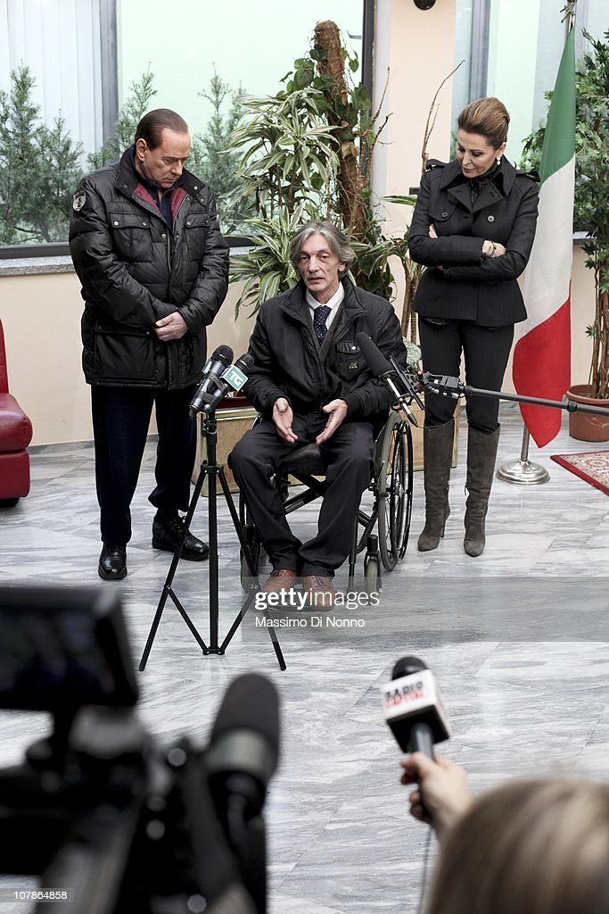 Italian Prime Minister <a gi-track='captionPersonalityLinkClicked' href=/galleries/search?phrase=Silvio+Berlusconi&family=editorial&specificpeople=201842 ng-click='$event.stopPropagation()'>Silvio Berlusconi</a> (L) and Italian politician <a gi-track='captionPersonalityLinkClicked' href=/galleries/search?phrase=Daniela+Santanche&family=editorial&specificpeople=643237 ng-click='$event.stopPropagation()'>Daniela Santanche</a> (R) face media alongside Alberto Torregiani, the son Pierluigi Torregiani, at Linate military airport on January 04, 2011 in Milan, Italy. Alberto Torregiani was shot in the back and was left paralysed during the same gunfight in which his father jeweler Pierluigi Torregiani was killed by militant group PAC (Armed Proletarians for Communism) in 1979. Italy has recalled its ambassador to Brazil to following former Brazilian President Luiz Inacio Lula da Silva's decision on his final day in office not to approve the extradition of Cesare Battisti, deemed responsible for the attack and convicted for a string of murders in the 1970s for which he was tried and convicted in absentia.