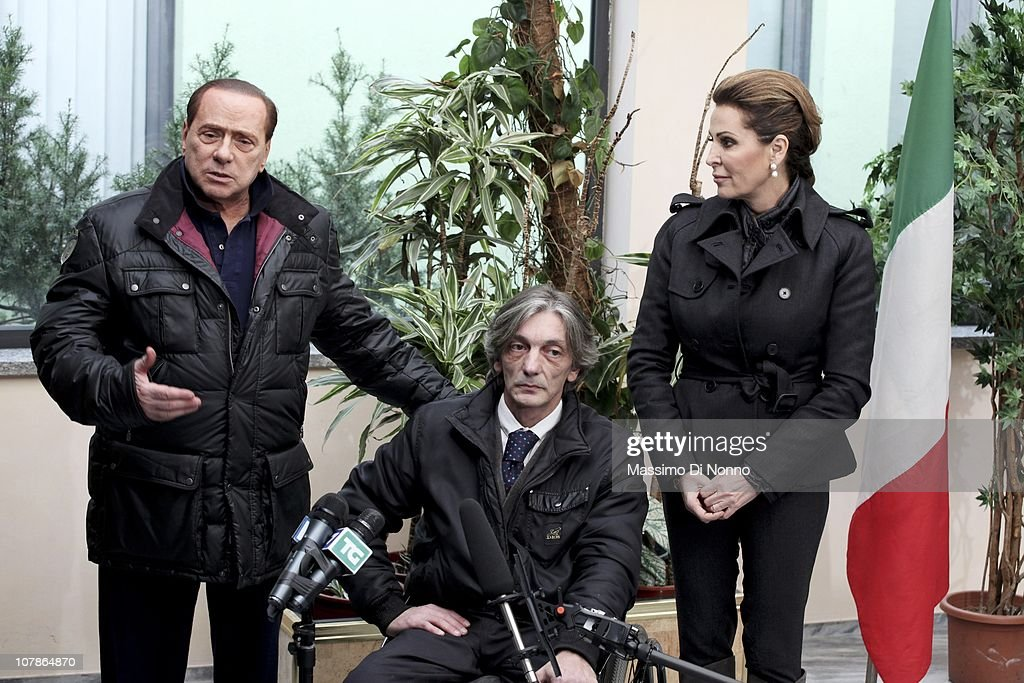 Italian Prime Minister Silvio Berlusconi (L) and Italian politician Daniela Santanche (R) face media alongside Alberto Torregiani, the son Pierluigi Torregiani, at Linate military airport on January 04, 2011 in Milan, Italy. Alberto Torregiani was shot in the back and was left paralysed during the same gunfight in which his father jeweler Pierluigi Torregiani was killed by militant group PAC (Armed Proletarians for Communism) in 1979. Italy has recalled its ambassador to Brazil to following former Brazilian President Luiz Inacio Lula da Silva's decision on his final day in office not to approve the extradition of Cesare Battisti, deemed responsible for the attack and convicted for a string of murders in the 1970s for which he was tried and convicted in absentia.