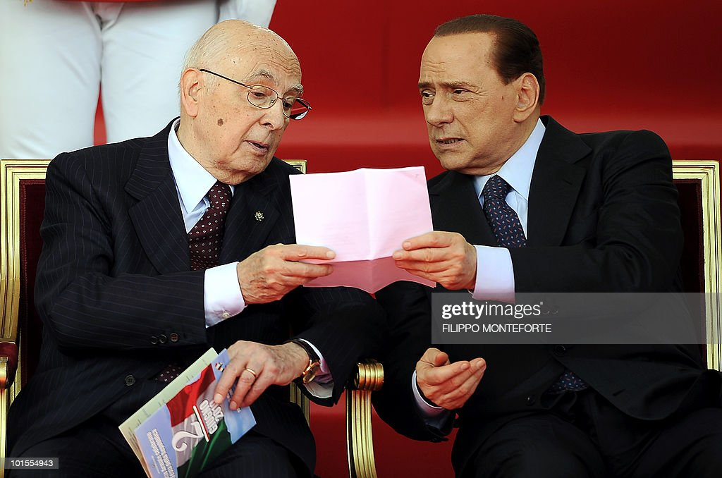 Italian Prime Minister Silvio Berlusconi (R) and Italian Republic President Giorgio Napolitano share a sheet of paper during the celebrations marking the country's Republic Dayin central Rome on June 2, 2010. Italian armed forces celebrate the 64th anniversary of Italy's birth as a Republic parading infront of the italian istitutional members. AFP PHOTO / Filippo MONTEFORTE