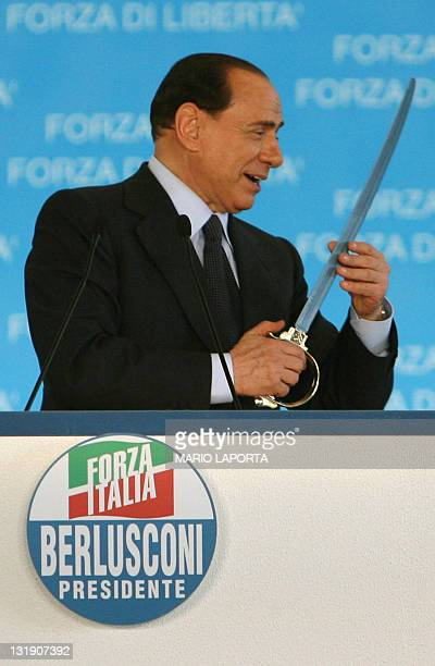 Italian Prime Minister Silvio Berlusconi centreright coalition leader gestures with sword during a campaign meeting of Forza Italia 25 March 2006 in...
