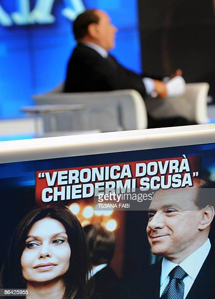 Italian Prime Minister Silvio Berlusconi is seen while a portrait of his wife Veronica Lario and him is projected reading ' Veronica will have to...